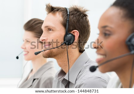 Closeup Of Happy Telephone Operators In A Row - stock photo