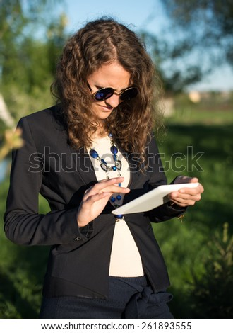 closeup of happy woman in glasses using tablet pc in the park - stock photo