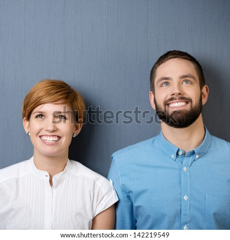 Closeup of happy young businessman and businesswoman looking up isolated over blue background - stock photo