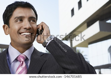 Closeup of happy young businessman using cell phone in front of building - stock photo