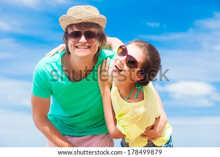 Closeup of happy young couple in sunglasses having fun on tropical beach