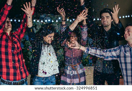 Closeup of happy young friends raising their arms and having fun among the colorful confetti cloud in a outdoors party. Friendship and celebrations concept. - stock photo
