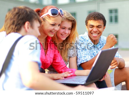 Closeup of happy young friends using laptop