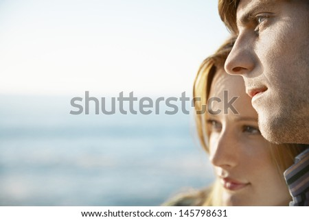 Closeup of happy young man with girlfriend by ocean looking away - stock photo