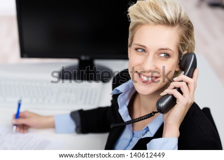 Closeup of happy young woman using phone while looking up in office - stock photo