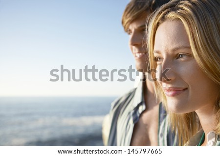 Closeup of happy young woman with man in background by ocean - stock photo