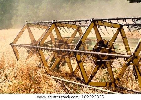 Closeup of harvesting machinery detail while working the field - stock photo