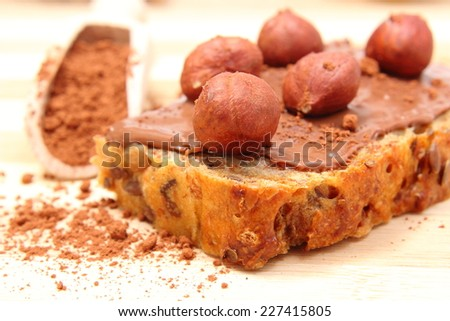 Closeup of hazelnut lying on slices of bread with chocolate cream, heap of cocoa on wooden spoon in background - stock photo