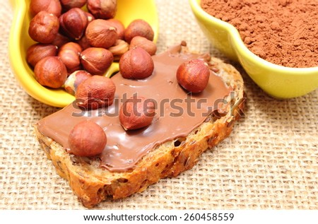 Closeup of hazelnut lying on slices of bread with chocolate cream, heap of hazelnut and cocoa in background - stock photo
