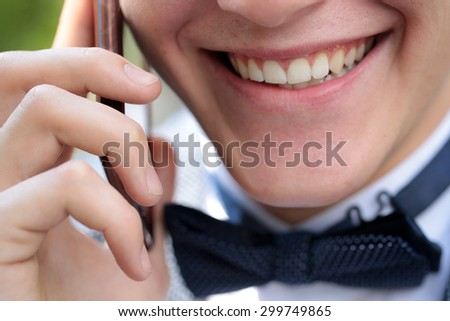 Closeup of healthy clean teeth in open male mouth in beautiful smile on young emotional happy shaven face of man in black bow tie on white collar holding mobile phone and speaking, horizontal photo - stock photo