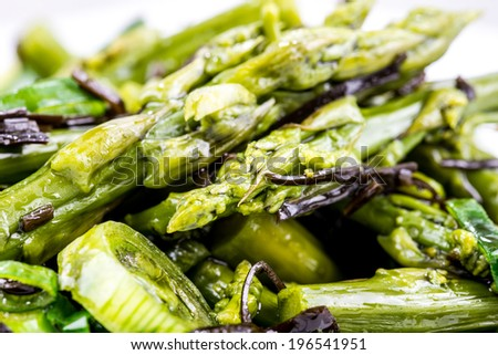Closeup of healthy delicious asparagus salad with spring onion and arame seaweed.