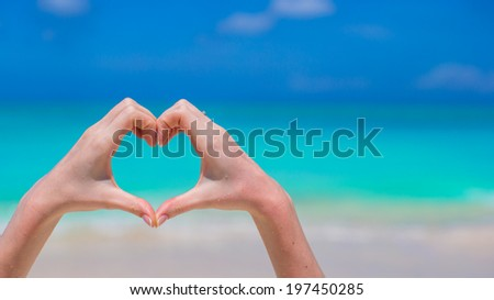 Closeup of heart made by hands background turquoise water - stock photo