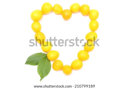 Closeup of heart shaped yellow mirabelle. Isolated on white background
