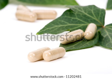 Closeup of herbal supplement pills and fresh ivy leaves best suited for alternative medicine ads. Shallow DOF. - stock photo