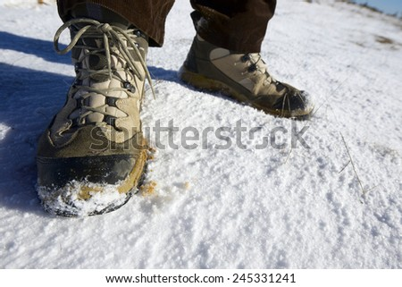Closeup of hiking boots in the snow. - stock photo