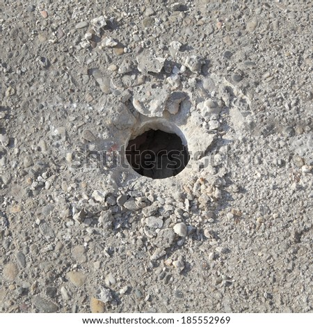 Closeup of hole in concrete after demolishing with jackhammer tool at construction site - stock photo