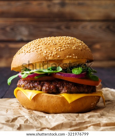 Closeup of home made burger on wooden background. - stock photo