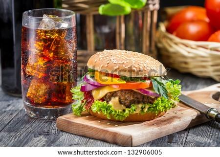 Closeup of homemade hamburger and a Coke with ice - stock photo