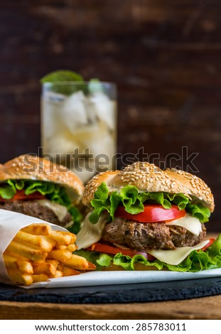 Closeup of Homemade Hamburger with Fresh Vegetables and Drink with Ice in Background