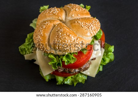 Closeup of Homemade Hamburger with Fresh Vegetables on Stone Background - stock photo