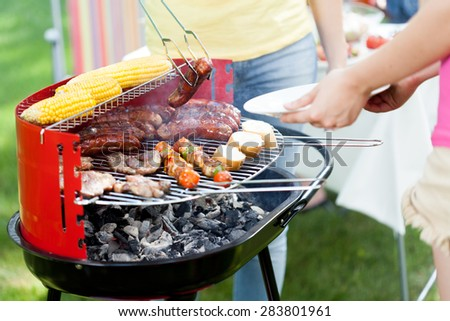 Closeup of host serving woman grilled sausage