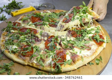 Closeup of Hot Delicious-Looking Pizza With Pepperoni, Cheese and Ham on Wooden Board Ready to Eat - stock photo