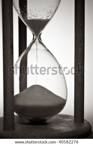 closeup of hourglass in warm black and white - stock photo