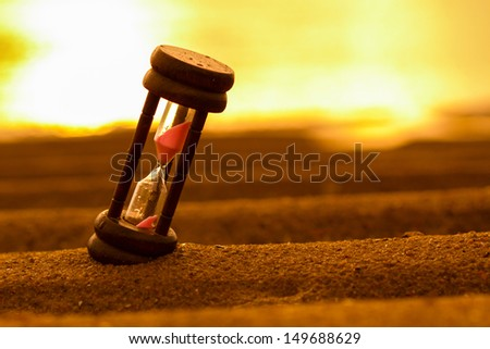 Closeup of hourglass on the sand.Timer Beach Sunrise - stock photo