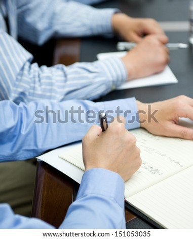 Closeup of human hand writing at a conference. - stock photo