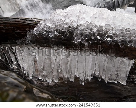 Closeup of icicles and frozen water surrounding a  log at the bottom of a waterfall. - stock photo