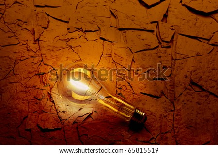 Closeup of Illuminated light bulb on parched red desert surface