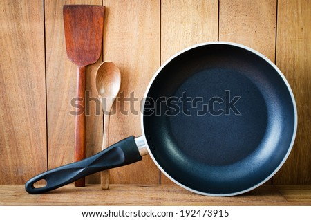 Closeup of  iron frying pan and wooden utensils on wood wall background .  - stock photo