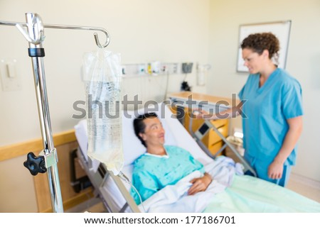 Closeup of IV bag with nurse and patient looking at each other in background at hospital - stock photo