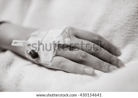 Closeup of iv drip in woman hand on bed in hospital, Focus on the hand of a patient, black and white photo - stock photo