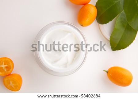 Closeup of jar of moisturizing face cream and fresh citrus - stock photo