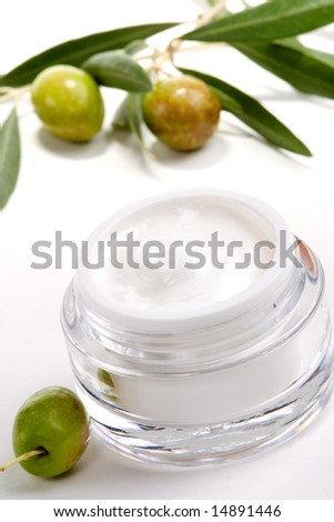 Closeup of jar of moisturizing face cream and twig with green olives. - stock photo