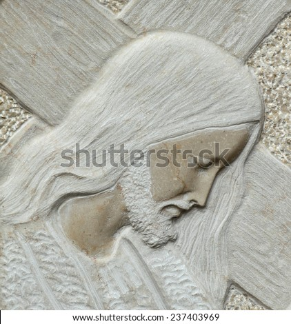 closeup of Jesus holding a cross- detail of relief in stone - stock photo