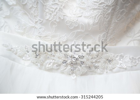 Closeup of jewelry embroidery on wedding dress - stock photo