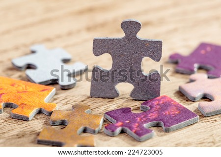 Closeup of jigsaw puzzle piece on a table. Shallow depth of field - stock photo