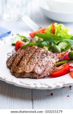 Closeup of juicy grilled beef steak with salad - stock photo