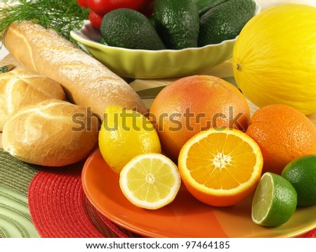 Closeup of juicy oranges and fresh rolls with avocados in a background - stock photo