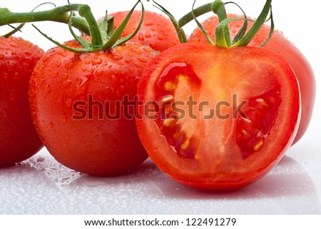 closeup of juicy tomato sliced with drops against white background - stock photo