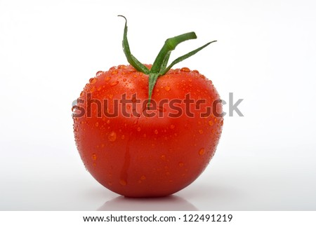closeup of juicy tomato with drops isolated against a white background