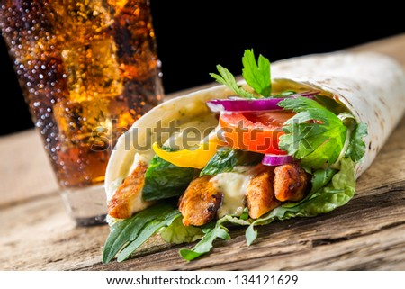 Closeup of kebab with fresh vegetables and chicken on black background