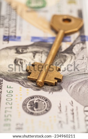 Closeup of key on hundred dollar bills