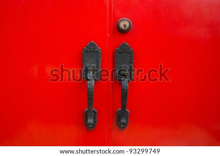 Closeup of keyhole and handle on red door - stock photo