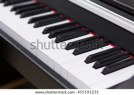 Closeup of keys of piano. Closeup of piano keys. Close frontal view. Piano keyboard background with selective focus. - stock photo