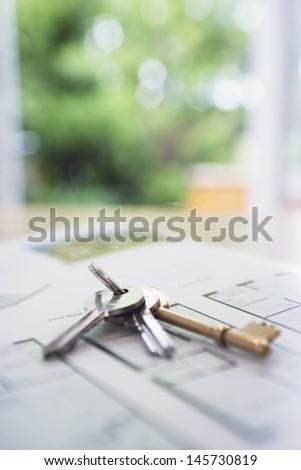 Closeup of keys on blueprint of new home - stock photo
