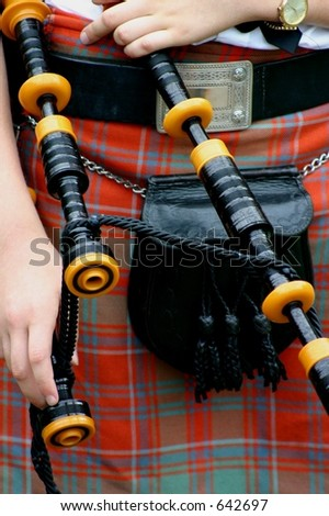 Closeup of kilt, sporan and bagpipes of young scotswoman