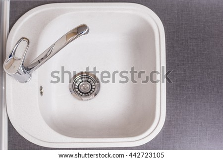 Closeup of Kitchen Marble Sink and Installed New Faucet. Indoors Shot. Horizontal image Composition - stock photo
